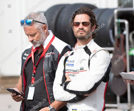 Stock Photo of Prince Carl Philip (R) of Sweden waits to compete in one of the VIP cars during the Scandinavian Porsche Carrera Cup at the Gellerasen Motor stadium in Karlskoga, Sweden, 18 August 2019. Prince Carl Philip of Sweden, the only son of Swedish King Carl Gustav and Queen Silvia, has already been competing as a racing driver in various touring car championships and endurance races in Scandinavia in the past. Man on left is not identified.