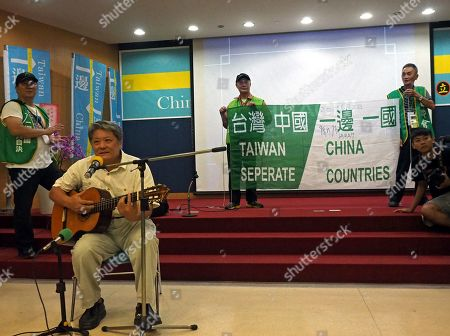 Stock Photo of A man (L) sings songs while two men (R) display a banner with Chinese and English words 'Taiwan China Are Separate Counties' at a news conference announcing the launch of the Taiwan Action Party Alliance (TAPA) in Taipei, Taiwan, 18 August 2019. News report said that TAPA is launched by ex-president Chen Shui-bian but he cannot become its leader as he is serving time for corruption. Chen launched TAPA because he is angry that President Tsai Intg-wen favours maintaining the status quo in Taiwan-China ties instead of seeking Taiwan independence. PATA's goal is to seek Taiwan independence and to change Taiwan's name from the Republic of China to Republic of Taiwan. China sees Taiwan as its breakaway province and has vowed to recover Taiwan by force if Taipei indefinitely delays holding unification talks with Beijing or seeks independence.