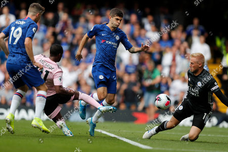 Chelsea's Christian Pulisic, center, vies for the ball with Leicester's Ricardo Pereira, 2nd left, in front of Leicester's goalkeeper Kasper Schmeichel, right, during the English Premier League soccer match between Chelsea and Leicester City at Stamford Bridge stadium in London