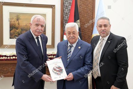 Palestinian President Mahmoud Abbas rceives the annual report of the Palestinian International Cooperation Agency of 2018 from the Palestinian foreign Minister Riyad al-Maliki