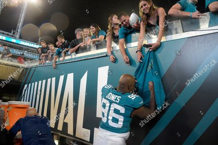 Jacksonville Jaguars defensive end Datone Jones (96) signs autographs for fans after an NFL preseason football game against the Philadelphia Eagles, in Jacksonville, Fla