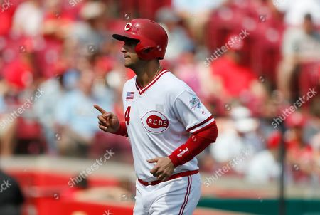 Cincinnati Reds' Jose Iglesias reacts as he scores on a bases loaded walk by Jose Perez, delivered by St. Louis Cardinals relief pitcher Andrew Miller, during the seventh inning of a baseball game, in Cincinnati