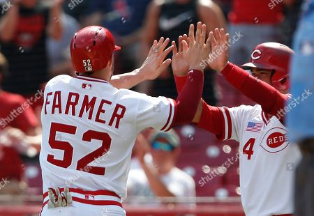 Cincinnati Reds' Kyle Farmer (52) and Jose Iglesias (4) celebrate after scoring on a single by Tucker Barnhart, off St. Louis Cardinals relief pitcher Carlos Martinez, during the ninth inning of a baseball game, in Cincinnati