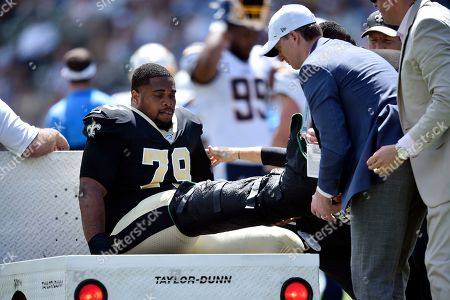 New Orleans Saints' Chris Clark goes down with an injury during the first half of a preseason NFL football game against the Los Angeles Chargers, in Carson, Calif