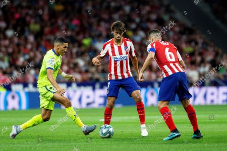 Atletico Madrid's Portuguese forward Joao Felix (C) and Koke Resurreccion (R) vie for the ball with Getafe CF's Moroccan midfielder Faycal Fajr (L) during their LaLiga game at Wanda Metropolitano Stadium in Madrid, Spain, 18 August 2019.