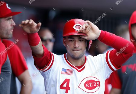 Cincinnati Reds' Jose Iglesias reacts in the dugout after scoring on a bases loaded walk by Jose Perez, delivered by St. Louis Cardinals relief pitcher Andrew Miller, during the seventh inning of a baseball game, in Cincinnati