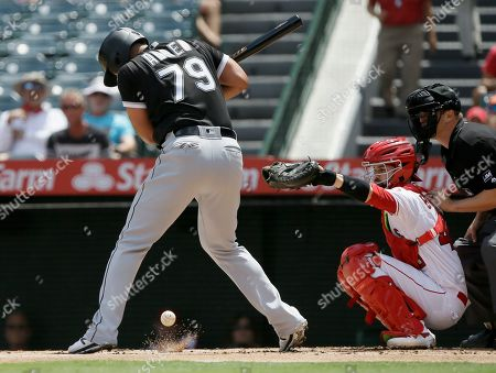 Chicago White Sox' Jose Abreu, left, is hit by a pitch with Los Angeles Angels catcher Anthony Bemboom, center, and home plate umpire Chris Segal watching during the first inning of a baseball game in Anaheim, Calif