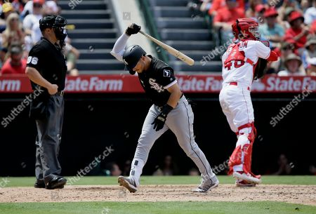 Chicago White Sox' Yolmer Sanchez, center, reacts after striking out, with Los Angeles Angels catcher Anthony Bemboom, right, throwing the ball out and home plate umpire Chris Segal, left, looking away during the fifth inning of a baseball game in Anaheim, Calif