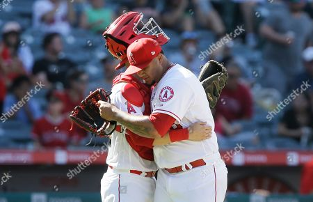 Los Angeles Angels relief pitcher Adalberto Mejia, right, hugs catcher Anthony Bemboom after the Angels defeat the Chicago White Sox 9-2 in a baseball game in Anaheim, Calif