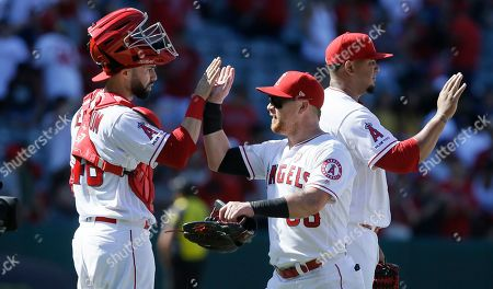 Los Angeles Angels' Kole Calhoun, center, celebrates with catcher Anthony Bemboom, left, after the Angels defeat the Chicago White Sox 9-2 in a baseball game in Anaheim, Calif