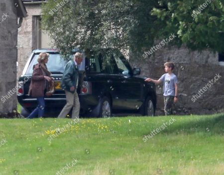 Prince Philip hands his cushion to James Viscount Severn to carry to the car for him
