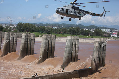 An Indian Air Force helicopter rescues fishermen who were trapped in floodwaters in the River Tawi in Jammu, India, . Water levels in many rivers in north India have risen following heavy monsoon rains