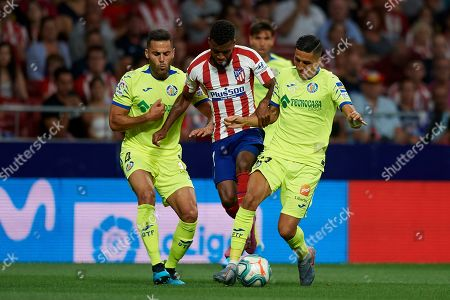 Bruno Gonzalez and Faycal Fajr of Getafe and Thomas Lemar of Atletico Madrid compete for the ball