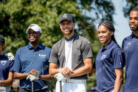 Howard University President Wayne Frederick, left, and Basketball guard Stephen Curry, center, pose for photographs with Howard student caddies before teeing off together at Langston Golf Course in Washington, following a news conference where Curry announced that he would be sponsoring the creation of men's and women's golf teams at Howard University