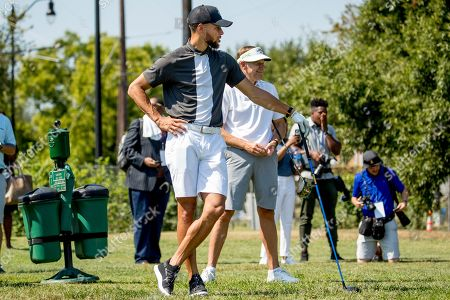 Basketball guard Stephen Curry, center, stands with Callaway Golf Company CEO Oliver Brewer III, center right, before teeing off at Langston Golf Course in Washington, after Curry announced that he would be sponsoring the creation of men's and women's golf teams at Howard University