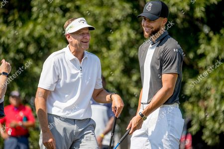 Basketball guard Stephen Curry, right, speaks with Callaway Golf Company CEO Oliver Brewer III, left, before teeing off at Langston Golf Course in Washington, after Curry announced that he would be sponsoring the creation of men's and women's golf teams at Howard University