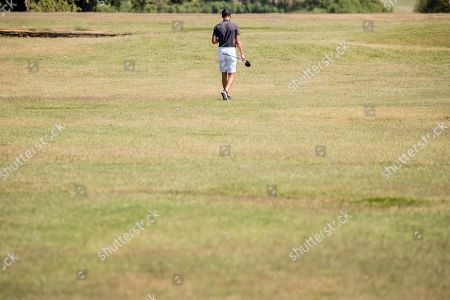 Basketball guard Stephen Curry walks the first hole at Langston Golf Course in Washington, following a news conference where Curry announced that he would be sponsoring the creation of men's and women's golf teams at Howard University