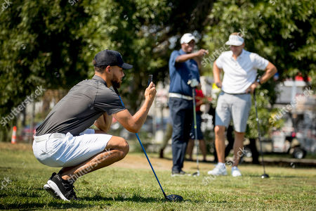 Golden State Warriors guard Stephen Curry films Howard student Otis Ferguson as he tees off at Langston Golf Course in Washington, following an announcement Curry would be sponsoring men's and women's golf teams at Howard University
