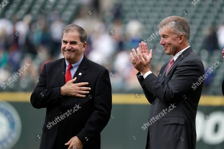 Tim Mead, left, president of the National Baseball Hall of Fame and Museum, motions while being introduced as Kevin Mather, Seattle Mariners president and CEO, applauds during a ceremony honoring former Seattle Mariners designated hitter Edgar Martinez for his recent induction into the Baseball Hall of Fame before a baseball game between the Mariners and Tampa Bay Rays, in Seattle