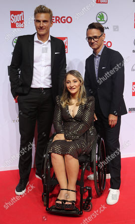 Stock Picture of German former cyclist Kristina Vogel poses with German cyclist Marcel Kittel (L) and Vogel's partner Michael Seidenbrecher (R) on the red carpet at the Sportbild Award in Hamburg, Germany, 19 August 2019. The newspaper's award is granted to athletes since 2003.