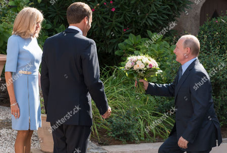 Brigitte Trogneux, Emmanuel Macron and Vladimir Putin with a bouquet of flowers