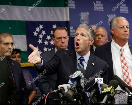 "Police Benevolent Association Patrick J. Lynch, center, gestures during a press conference at PBA headquarters following a decision to terminate NYPD Officer Daniel Pantaleo, who was involved in the chokehold death of Eric Garner five years ago, in New York. Pantaleo's attorney Stuart London is at right. Garner's dying cries of ""I can't breathe"" fueled a national debate over race and police use of force. Lynch said the PBA will call for a ""no confidence vote"" on the mayor and the police commissioner as a statement, the NYPD flag behind Lynch hangs upside down"