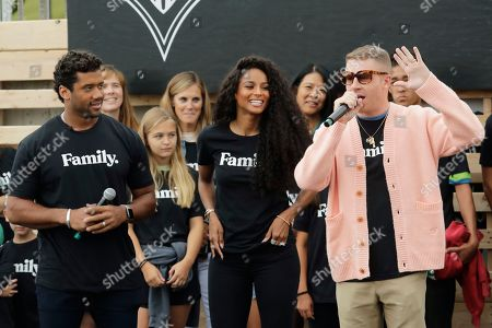 Seattle Seahawks NFL football quarterback Russell Wilson, left, and his wife, pop singer Ciara, center, listen as hip-hop artist Macklemore, right, speaks, during an event in Seattle held to introduce themselves and others as new members of the MLS soccer Seattle Sounders team's ownership group
