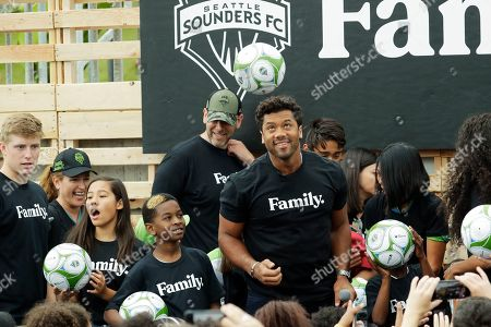 Seattle Seahawks NFL football quarterback Russell Wilson heads a soccer ball, during an event in Seattle held to introduce Wilson, his wife, pop singer Ciara, hip-hop artist Macklemore, and others as new members of the Seattle Sounders MLS soccer team's ownership group