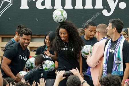 Pop singer Ciara, center, the wife of Seattle Seahawks NFL football quarterback Russell Wilson, left, heads a soccer ball, during an event in Seattle held to introduce the couple, hip-hop artist Macklemore, and others as new members of the Seattle Sounders MLS soccer team's ownership group