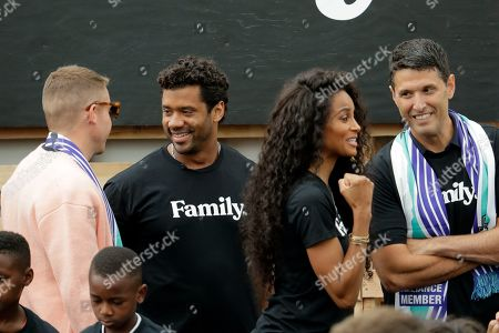 From left to right, hip-hop artist Macklemore, Seattle Seahawks NFL football quarterback Russell Wilson, Wilson's wife, pop singer Ciara, and former Microsoft executive Terry Myerson visit, during an event in Seattle held to introduce themselves and others as new members of the MLS soccer Seattle Sounders team's ownership group