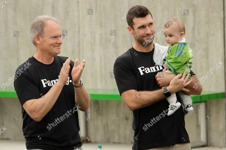 Brian Schmetzer, left, head coach of the Seattle Sounders MLS soccer team, stands with Sounders forward Will Bruin, during an event in Seattle held to introduce Seattle Seahawks NFL football quarterback Russell Wilson, his wife, pop singer Ciara, hip-hop artist Macklemore, and others as new members of the MLS soccer team's ownership group