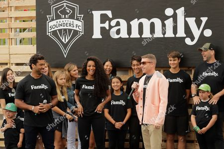 Seattle Seahawks NFL football quarterback Russell Wilson, left, and his wife, pop singer Ciara, center, listen as hip-hop artist Macklemore, center-right, speaks, during an event in Seattle held to introduce themselves and others as new members of the MLS soccer Seattle Sounders team's ownership group