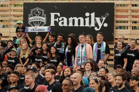 New members of the Seattle Sounders MLS soccer team ownership group, including former Microsoft executive Terry Myerson, fourth from right, hip-hop artist Macklemore, sixth from right, Seattle Seahawks NFL football quarterback Russell Wilson, eighth from right, and Wilson's wife -- pop singer Ciara, seventh from right, pose for a photo with fans, during an event in Seattle held to introduce the new owners