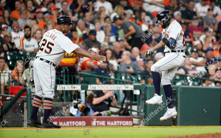 Detroit Tigers' Ronny Rodriguez, right, celebrates with third base coach Dave Clark (25) after hitting a home run against the Houston Astros during the sixth inning of a baseball game, in Houston