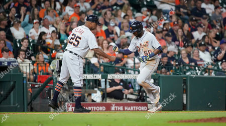 Detroit Tigers' Travis Demeritte (50) celebrates with third base coach Dave Clark (25) after hitting a home run against the Houston Astros during the seventh inning of a baseball game, in Houston