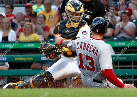 Stock Picture of Pittsburgh Pirates catcher Elias Diaz, top, looks to tag Washington Nationals' Asdrubal Cabrera (13) who was trying to score from first on a double by Matt Adams in the second inning of a baseball game, in Pittsburgh. Cabrera was out