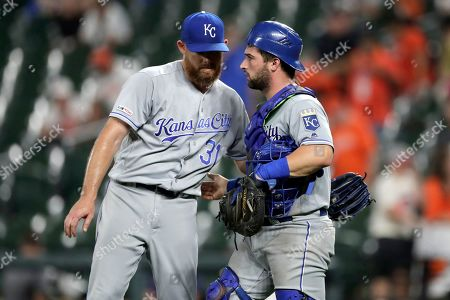 Kansas City Royals relief pitcher Ian Kennedy (31) and catcher Nick Dini (33) celebrate after defeating the Baltimore Orioles in a baseball game, in Baltimore
