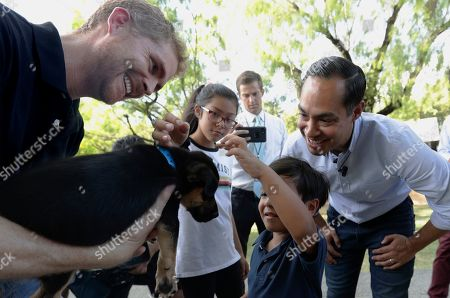 Stock Picture of Julian Castro, Cristian Castro, Carina Castro. Democratic presidential candidate and former Housing Secretary Julian Castro, right, with his son Cristian, and daughter Carina, visit with Ivan, a puppy up for adoption, during a stop at the Animal Defense League of Texas shelter, in San Antonio