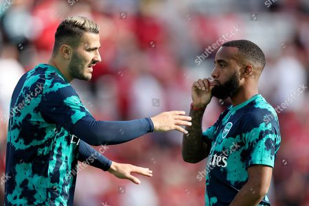 Alexandre Lacazette of Arsenal holds onto his lips as Sead Kolasinac speaks with him during the pre-match warm-up
