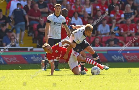 Barnsley's Luke Thomas is floored by Luton's James Bree.