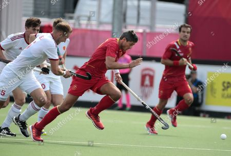 Spain's Xavi Lleonart, center, vies for the ball against England's David Ames, left, during a men's European Championships field hockey match between Spain and England at the Wilrijkse Plein, Antwerp, Belgium