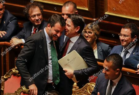 Italian Premier Giuseppe Conte, right, shares a word with Deputy-Premier Matteo Salvini before addressing the Senate in Rome, . The political showdown on Tuesday was triggered two weeks ago by hard-line Interior Minister Matteo Salvini, known across Europe for his tough stance against migrants, when he pulled the plug on the shaky populist coalition forged only 14 months earlier between his right-wing League and the anti-establishment 5-Star Movement