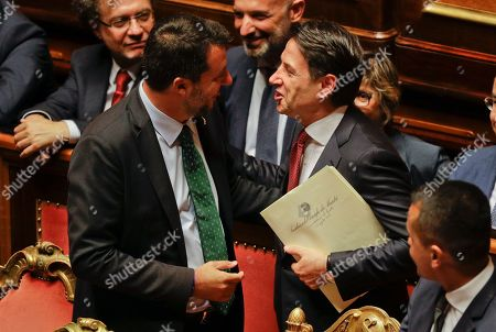 Italian Premier Giuseppe Conte, right, talks to Deputy-Premier Matteo Salvini before addressing the Senate in Rome, . The political showdown on Tuesday was triggered two weeks ago by hard-line Interior Minister Matteo Salvini, known across Europe for his tough stance against migrants, when he pulled the plug on the shaky populist coalition forged only 14 months earlier between his right-wing League and the anti-establishment 5-Star Movement