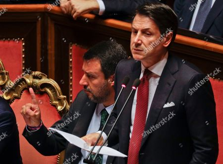 Italian Premier Giuseppe Conte, right, speaks as Deputy-Premier Matteo Salvini gestures beside him, at the Senate in Rome, . The political showdown on Tuesday was triggered two weeks ago by hard-line Interior Minister Matteo Salvini, known across Europe for his tough stance against migrants, when he pulled the plug on the shaky populist coalition forged only 14 months earlier between his right-wing League and the anti-establishment 5-Star Movement
