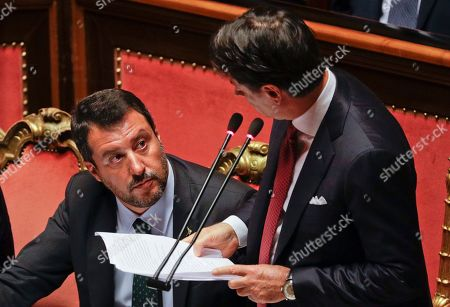 Italian Premier Giuseppe Conte, right, looks at Deputy-Premier Matteo Salvini as he addresses the Senate in Rome, . The political showdown on Tuesday was triggered two weeks ago by hard-line Interior Minister Matteo Salvini, known across Europe for his tough stance against migrants, when he pulled the plug on the shaky populist coalition forged only 14 months earlier between his right-wing League and the anti-establishment 5-Star Movement