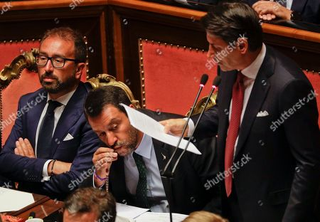 Italian Premier Giuseppe Conte addresses the Senate as Deputy-Premier Matteo Salvini kisses a rosary while sitting beside him, in Rome, . The political showdown on Tuesday was triggered two weeks ago by hard-line Interior Minister Matteo Salvini, known across Europe for his tough stance against migrants, when he pulled the plug on the shaky populist coalition forged only 14 months earlier between his right-wing League and the anti-establishment 5-Star Movement