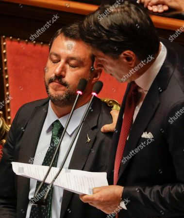 Italian Premier Giuseppe Conte, right, is flanked by Deputy-Premier Matteo Salvini as he addresses the Senate in Rome, . The political showdown on Tuesday was triggered two weeks ago by hard-line Interior Minister Matteo Salvini, known across Europe for his tough stance against migrants, when he pulled the plug on the shaky populist coalition forged only 14 months earlier between his right-wing League and the anti-establishment 5-Star Movement