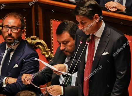 Italian Premier Giuseppe Conte addresses the Senate as Deputy-Premier Matteo Salvini holds a rosary while sitting beside him, in Rome, . The political showdown on Tuesday was triggered two weeks ago by hard-line Interior Minister Matteo Salvini, known across Europe for his tough stance against migrants, when he pulled the plug on the shaky populist coalition forged only 14 months earlier between his right-wing League and the anti-establishment 5-Star Movement