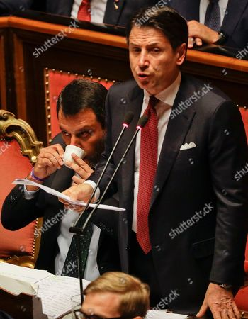 Stock Image of Italian Premier Giuseppe Conte addresses the Senate as Deputy-Premier Matteo Salvini its a coffee while sitting beside him, in Rome, . The political showdown on Tuesday was triggered two weeks ago by hard-line Interior Minister Matteo Salvini, known across Europe for his tough stance against migrants, when he pulled the plug on the shaky populist coalition forged only 14 months earlier between his right-wing League and the anti-establishment 5-Star Movement
