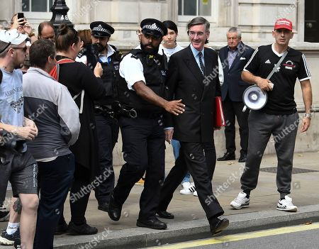 Jacob Rees-Mogg leaving the cabinet office with a police escort against anti Brexit protesters